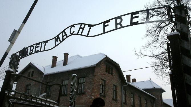 """A inscrição """"Arbeit macht frei"""" trava acima da entrada do campo principal do antigo campo de concentração em Auschwitz."""