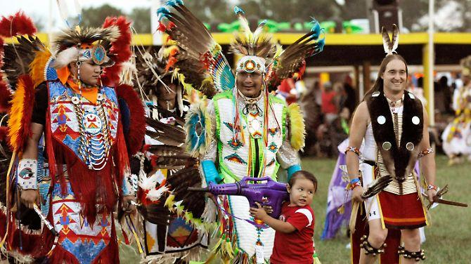 Uma criança brincando com uma arma de brinquedo na Nação Oglala Pow Wow, uma grande reunião na reserva Pine Indian Ridge Lakota.