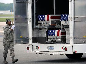 Os caixões contendo os corpos de soldados americanos que foram mortos no Afeganistão vai ser carregados em uma base em os EUA em uma van.