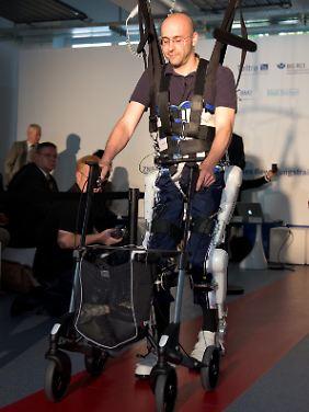 Philippe de Glisczynski demonstra a ação do robô, com a qual ele aprendeu a andar novamente.