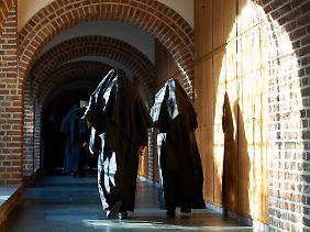 Benedikinerinnen im sonnendurchfluteten Kreuzgang in der Abtei Varensell.